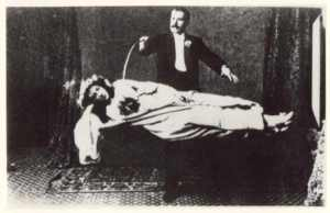 The great illusionist David Devant with a woman on a plank...